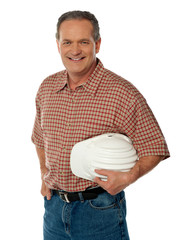 Smiling senior architect holding white safety hat