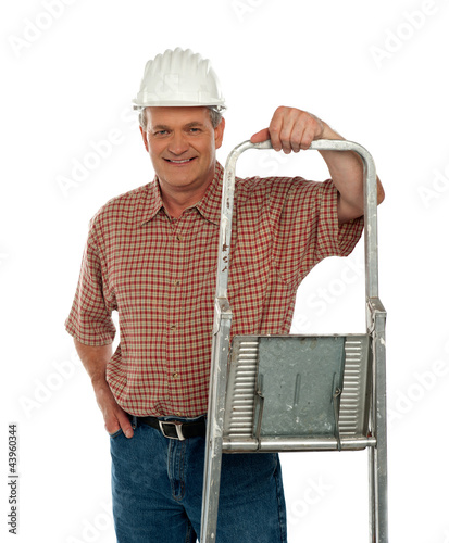 Smiling aged worker posing with ladder