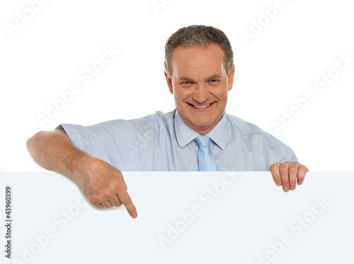 Casual male promoter pointing at blank billboard