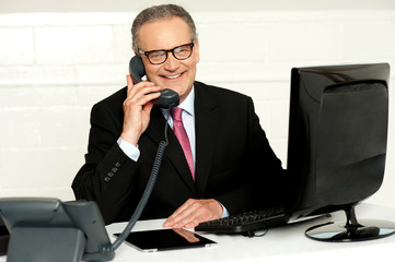 Senior businessman attending phone call