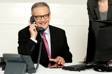 Aged businessman communicating on phone