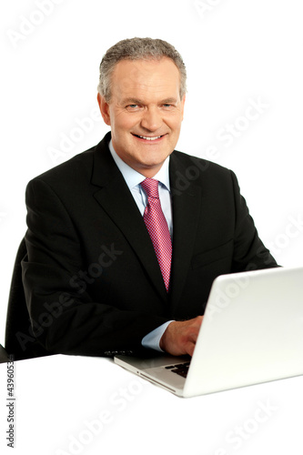 Confident businessman working on laptop
