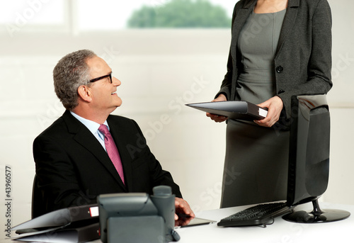 Smiling aged male boss looking at secretary