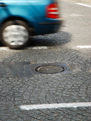 a car passing manhole cover on a paved road