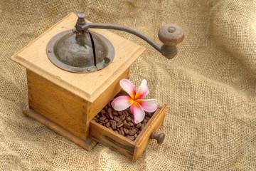 Café et fleur de frangipanier dans le titroi d'un vieux moulin