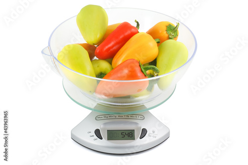Colorful peppers weighed on kitchen scales
