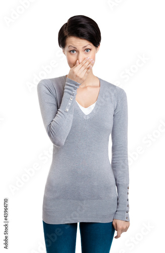 Young woman closes her nose with hand, isolated on white