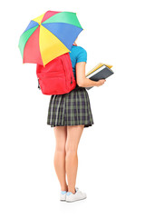 Full length portrait of a female student holding an umbrella