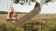 Pretty young girl swinging on hammock at sunset