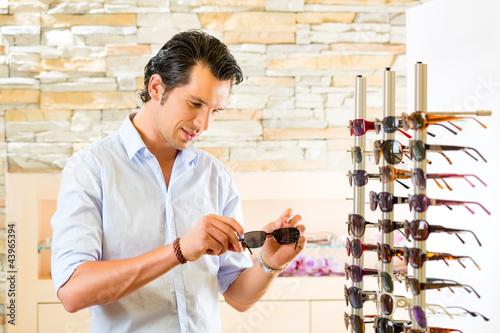Junger Mann beim Optiker kauft Sonnenbrille