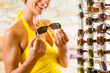 Junge Frau beim Optiker kauft Sonnenbrille