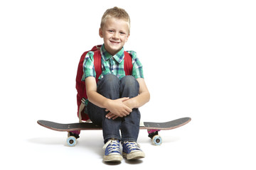 8 year old school boy with backpack sitting on a skateboard on w