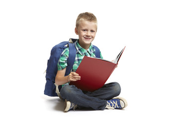 8 year old school boy with backpack reading on white background