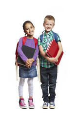 8 year old school boy and girl with packpacks holding books on w