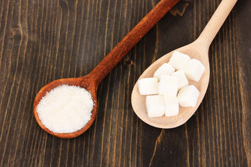 White sugar in spoons on wooden background