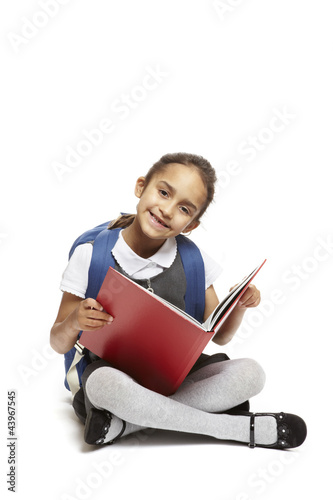 8 year old school girl sitting reading book on white background