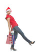 Happy woman in Christmas hat with shopping bags making step