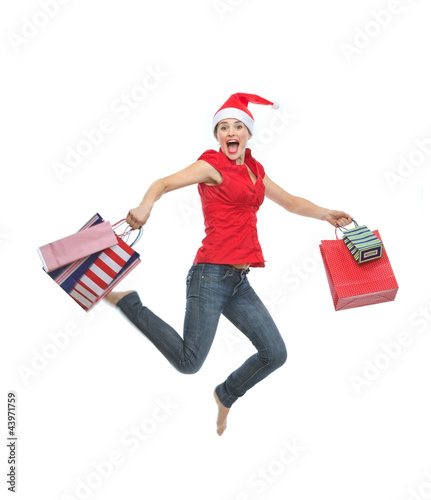 Happy woman in Christmas hat with shopping bags jumping