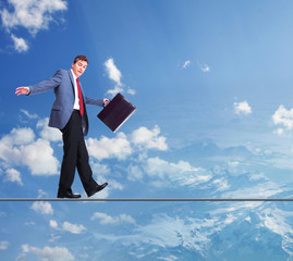 Businessman walking on rope in the sky.