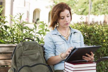 Young Female Student Outside on Bench Using Touch Tablet
