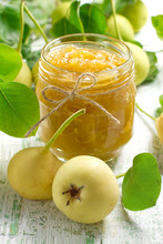 Pear jam in a glass jar and fresh fruits with leaves