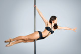 Fototapety Young sexy woman exercise pole dance against a gray background