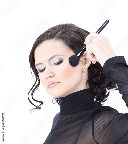 Beautiful woman with makeup brush near her face