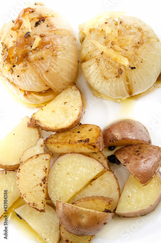 roasted onion with potatoes on a white plate