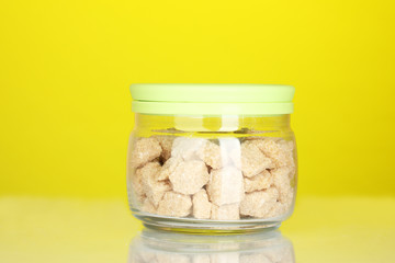 Jar with brown cane sugar lump on colorful background