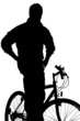 A silhouette of a  young boy posing on a bike
