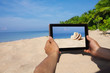 hands holding tablet pc on beach