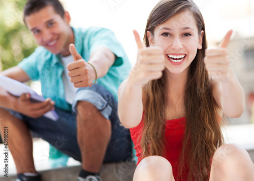 Teenage couple with thumbs up