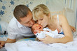 Happy mother and father kissing little newborn