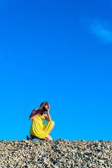 Junge Frau in gelbem Sommerkleid mit Kamera