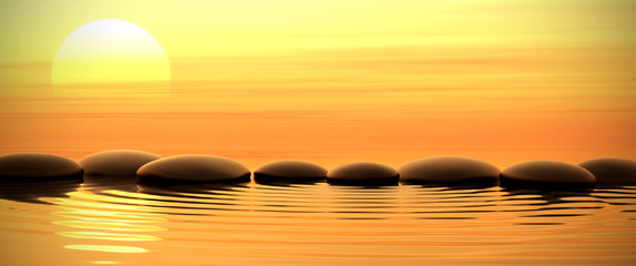 Zen stones in water on sunset