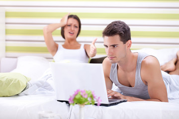 woman screaming at man while he works on laptop