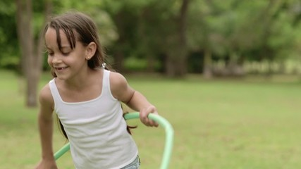 Happy young girl playing with hula-hoop in park