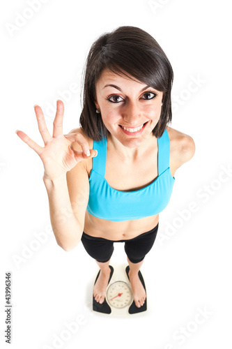 Fitness woman showing ok  on a weighing scale