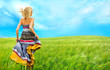 Portrait of romantic woman running across field