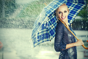Sexy girl under umbrella watching the rain