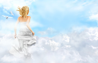 Young woman running across the clouds in the sky. Soul relaxatio
