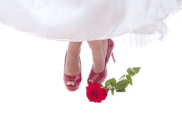 Bride feet in red shoes with rose
