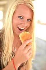 jeune femme mangeant un beignet