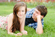 Young happy couple man and woman lying on green lawn and smiling