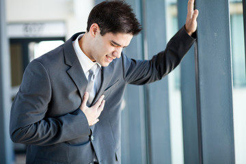 young businessman having heart attack or chest pain