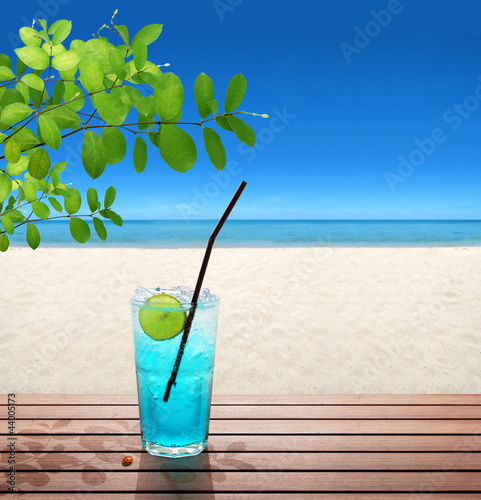 blue soda with lime under tree on the beach