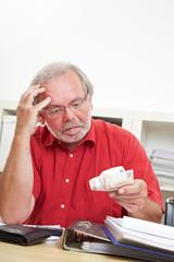Rentner schaut auf Geldscheine
