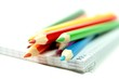 Colorful pencils with notebook on white background