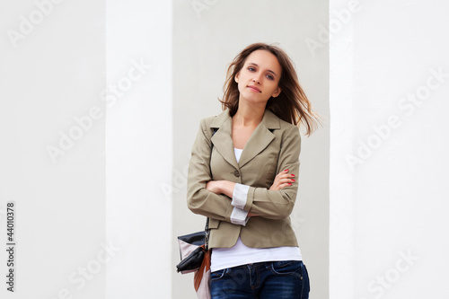 Young woman against a white wall