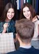 Two girls speak to salesperson